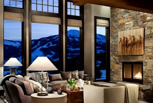 Contemporary Living Room with Hardwood floors, stone fireplace, High ceiling, Glass base table lamp, Round side table