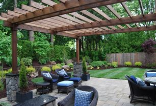 Traditional Patio with Wood pergola with stone base, exterior stone floors, Wicker outdoor furniture, Outdoor seating area