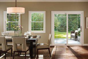 Modern Dining Room with Kenny Home Bronze Gilt Whistler pendant, Hardwood floors, Pendant light, Terra Dining Table