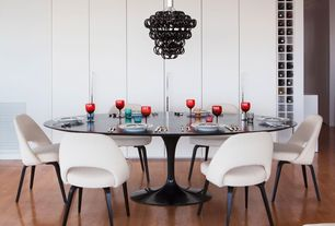 Contemporary Dining Room with Saarinen executive armless chair, High ceiling, Laminate floors, Chandelier