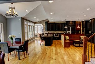 Craftsman Great Room with Arched window, Exposed beam, Chandelier, Hardwood floors, Built-in bookshelf, Pendant light