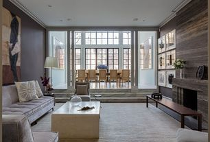 Contemporary Living Room with Sunken living room, Crown molding, Armless tufted velvet sofa, Cement fireplace, Columns
