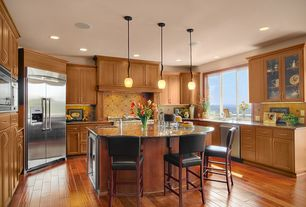 Traditional Kitchen with Casement, Pendant light, Standard height, Stone Tile, Custom hood, U-shaped, Built In Refrigerator