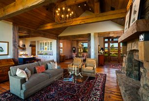 Country Living Room with Chandelier, stone fireplace, Exposed beam, Pottery barn landon upholstered armchair, High ceiling