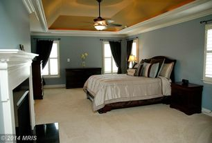 Traditional Master Bedroom with High ceiling, Crown molding, Ceiling fan, Carpet, Cement fireplace