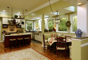Traditional Dining Room with Standard height, Wainscotting, Columns, specialty window, Hardwood floors, Crown molding