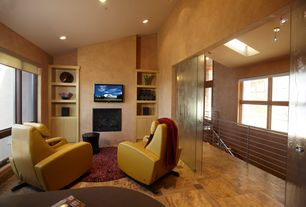 Contemporary Family Room with complex granite floors, picture window, can lights, insert fireplace, Built-in bookshelf