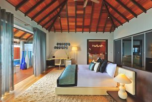 Contemporary Master Bedroom with Hardwood floors, Exposed beam, Ceiling fan, can lights, Built-in bookshelf, High ceiling