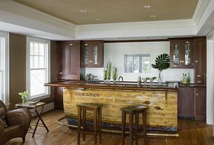 """Eclectic Bar with Crown molding, Built-in bookshelf, Hardwood floors, King armchair, United general supply 28"""" saddle stool"""