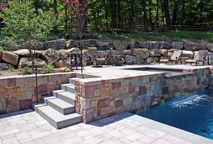 Rustic Patio with Exterior stone retaining walls, Outdoor seating, Pool waterfall feature