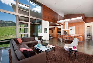 Modern Great Room with Poli white modern leather swivel lounge chair, High ceiling, Laminate floors, Built-in bookshelf