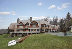 Craftsman Exterior of Home with Wood shingle siding, River rock wall, exterior columns, Wrap around porch, Outdoor pool