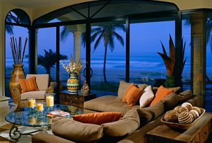 Tropical Living Room with Arched window, Transom window, sliding glass door, Concrete floors, Standard height