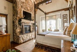 Rustic Master Bedroom with Home Image Island Chamfer Canopy Bed, stone fireplace, Arched window, Chandelier, Hardwood floors