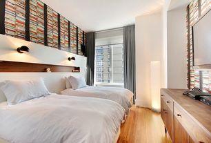 Contemporary Guest Bedroom with Hardwood floors, Built-in bookshelf, interior wallpaper