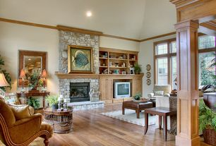 Craftsman Living Room with Hardwood floors, Built-in bookshelf, Crown molding, High ceiling, stone fireplace, Columns