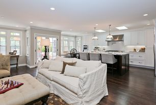 Traditional Great Room with Slipcover, French doors, Pendant light, can lights, Crown molding, Skylight, Hardwood floors