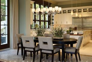Contemporary Dining Room with Built-in bookshelf, Daltile Marble Collection Crema Marfil Elegance Tile, Chandelier