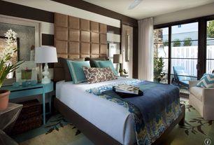 Contemporary Guest Bedroom with Ceiling fan, Hardwood floors, sliding glass door, Standard height
