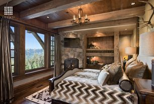 Rustic Guest Bedroom with Hooker furniture classique linen panel bed in medium chestnut - king, stone fireplace, Exposed beam