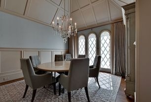 Traditional Dining Room with Wainscotting, High ceiling, Laminate floors, Chandelier, Arched window