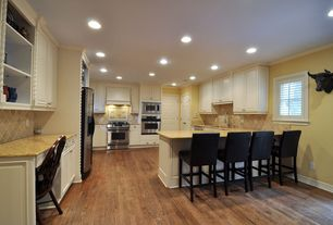 Traditional Kitchen with Hardwood floors, Framed Partial Panel, built-in microwave, Crown molding, gas range, Stone Tile