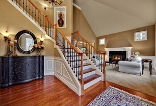 Traditional Staircase with stone fireplace, Chandelier, Cathedral ceiling, Casement, Columns, curved staircase, Wainscotting