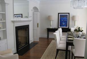 Contemporary Dining Room with specialty door, Cement fireplace, Chandelier, Crown molding, Hardwood floors