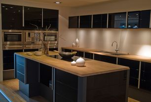 Modern Kitchen with Butcherblock countertop, L-shaped, Glass cooktop (smooth; touch buttons), Kitchen island, Glass panel
