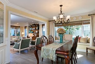 Traditional Dining Room with Window seat, Crown molding, Chair rail, Chandelier, Hardwood floors, Built-in bookshelf