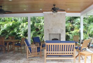 Tropical Porch with outdoor pizza oven, exterior stone floors, Porch swing, Fence