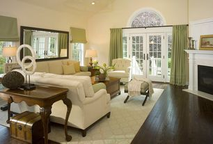 Traditional Living Room with Hardwood floors, Chandelier, Arched window, High ceiling, Cement fireplace, French doors