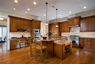 Traditional Kitchen with Pendant light, Crown molding, Breakfast bar, L-shaped, full backsplash, double wall oven, gas range