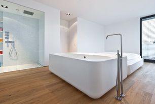 Contemporary Master Bathroom with Hardwood floors, frameless showerdoor, Freestanding, Master bathroom, Handheld showerhead