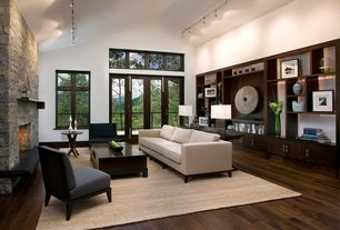 Contemporary Living Room with Armless slipper chair, Track lighting, Transom window, Hardwood floors, High ceiling