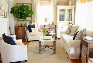 Living Room with Curved arm upholstered lounge chair, Distinctive designs fiddle leaf tree in planter, Hardwood floors