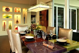 Modern Dining Room with Standard height, sliding glass door, can lights, Built-in bookshelf, Laminate floors, picture window
