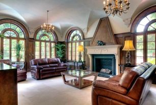 Mediterranean Living Room with stone fireplace, Arched window, Chandelier, Wainscotting, limestone floors
