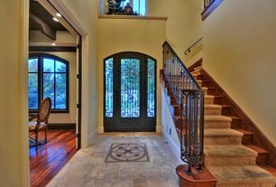 Mediterranean Entryway with sandstone tile floors, Cathedral ceiling, French doors
