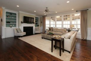 Traditional Living Room with can lights, Standard height, Fireplace, Built-in bookshelf, Wainscotting, Ceiling fan