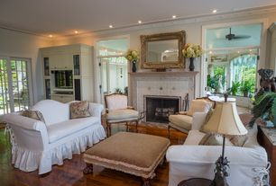 Traditional Living Room with French doors, White canvas sofa slipcover, Transom window, Laminate floors, stone fireplace