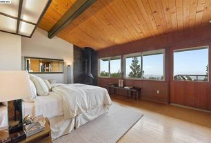 Modern Master Bedroom with Glass panel door, Fireplace, Hardwood floors, Wood Stove fireplace, Exposed beam, Casement
