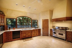 Traditional Kitchen with stone tile floors, Framed Partial Panel, U-shaped, Simple marble counters, Custom hood, can lights