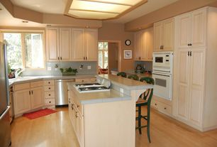 Country Kitchen with Casement, wall oven, simple marble tile counters, Stone Tile, can lights, Laminate floors, Drop-in sink