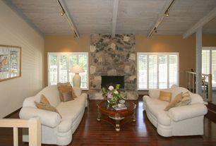 Rustic Living Room with Sunken living room, Mural, Laminate floors, Exposed beam, stone fireplace