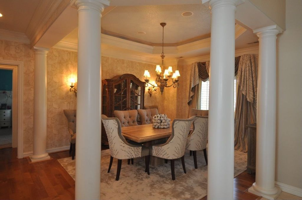 Traditional Dining Room with Columns, Wall sconce, Standard height, Chandelier, Crown molding, Hardwood floors