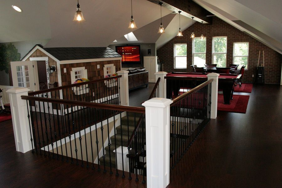Traditional Game Room with double-hung window, interior brick, Pendant light, High ceiling, Exposed beam, Laminate floors