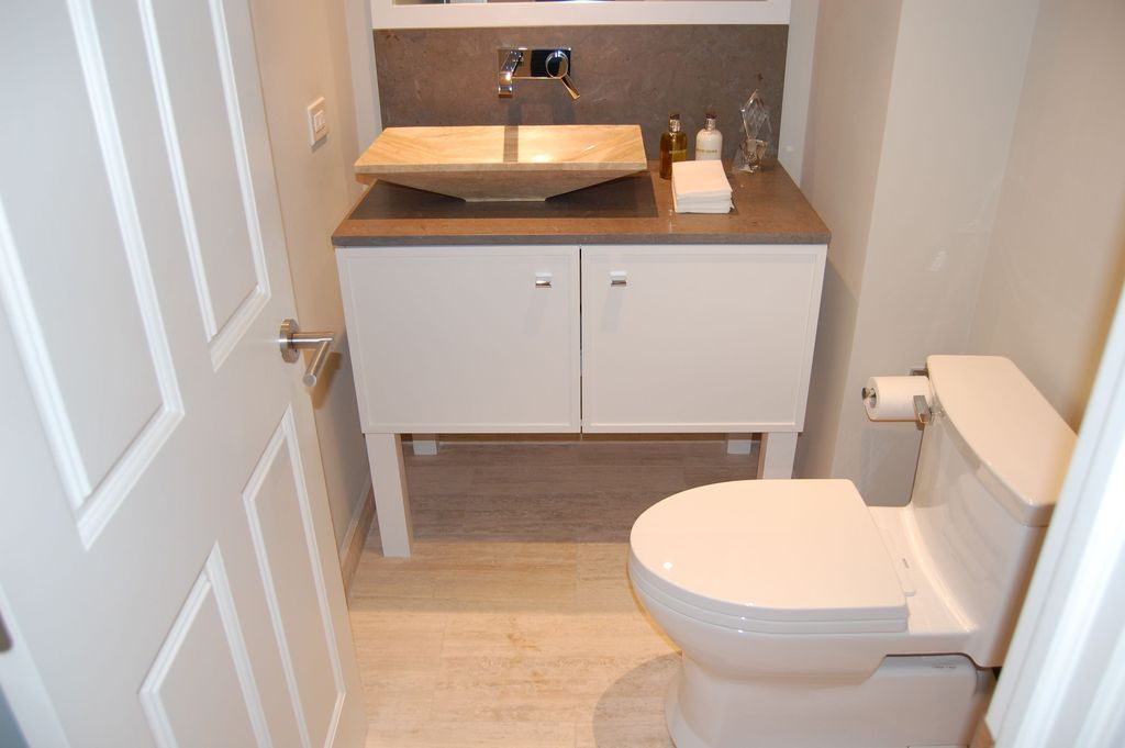 Contemporary Powder Room with Angled polished beige travertine vessel sink, specialty door, full backsplash, Paint