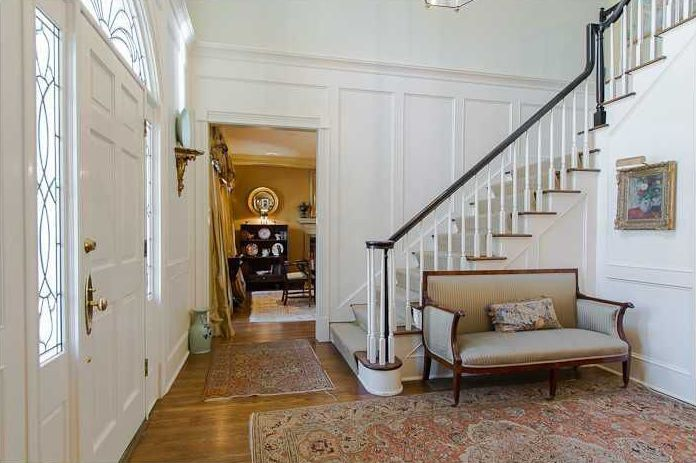 Traditional Entryway with six panel door, Wainscotting, Hardwood floors, Transom window, High ceiling