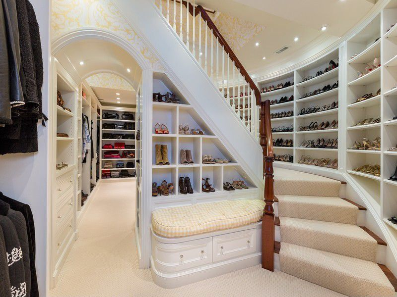 Traditional Closet with Woman's shoe storage open shelving, Built-in bench seating, Archway, Wood banister, Carpeted stairs